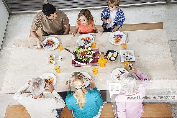 Großfamilie mit Salat und Saft am Esstisch