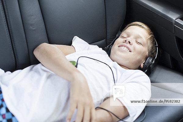 Jugendlicher Junge lächelt  während er Kopfhörer auf dem Rücksitz des Autos hört.