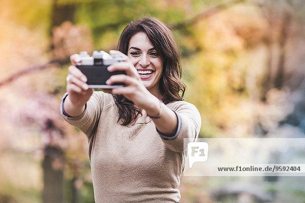 Junge Frau nimmt Selfie mit Spiegelreflexkamera im Herbstwald auf