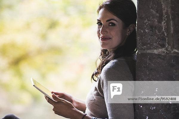 Porträt einer jungen Frau  die sich mit einem digitalen Tablett an die Wand lehnt. Porträt einer jungen Frau, die sich mit einem digitalen Tablett an die Wand lehnt.