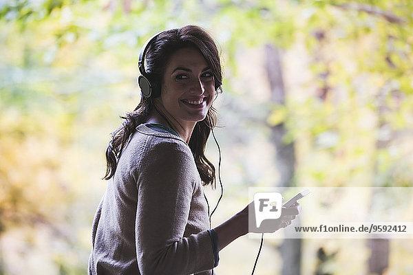 Porträt einer jungen Frau im Wald beim Hören von Kopfhörern Porträt einer jungen Frau im Wald beim Hören von Kopfhörern