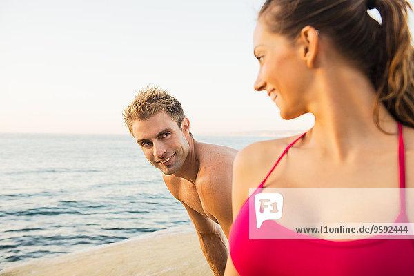 Mittlerer erwachsener Mann und junge Frau am Strand  die sich gegenseitig anschauen