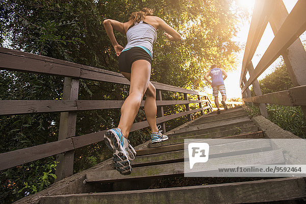 Mid adult man and young woman running up steps  rear  low angle view