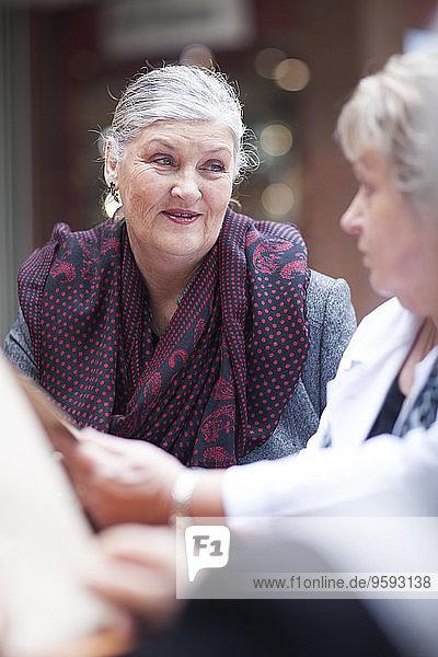 Porträt einer älteren Frau  die mit ihren Freundinnen in einem Straßencafé sitzt.