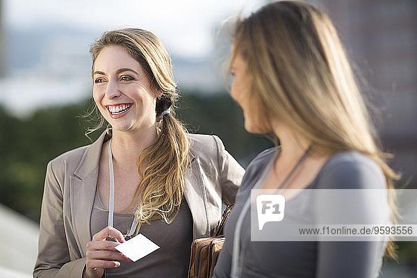 Porträt einer lächelnden Geschäftsfrau  die mit einer anderen kommuniziert.