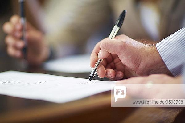 Geschäftsmann unterzeichnet Dokument im Sitzungssaal