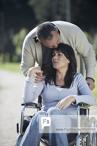 Mann tröstet traurige Frau im Rollstuhl
