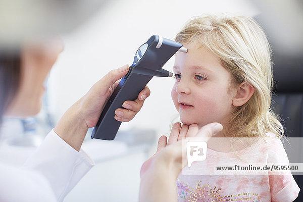 Augenarzt untersucht die Sehkraft des Mädchens