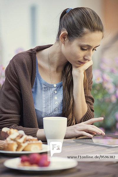 Junge Frau mit digitalem Tablett auf dem Außentisch