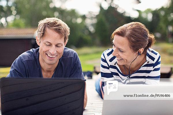 Lächelndes reifes Paar mit Laptops auf dem Pier liegend