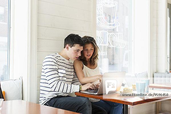 Paar mit Laptop beim Sitzen am Restauranttisch