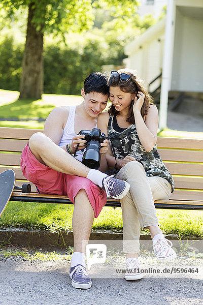 Ein glückliches Paar  das auf einer Bank im Park sitzt und Fotos vor der Kamera sieht.