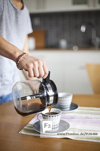 Mittelteil des Mannes  der Kaffee in die Tasse am Tisch gießt.