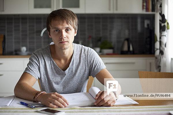 Porträt eines jungen Mannes  der bei Tisch im Haus studiert.