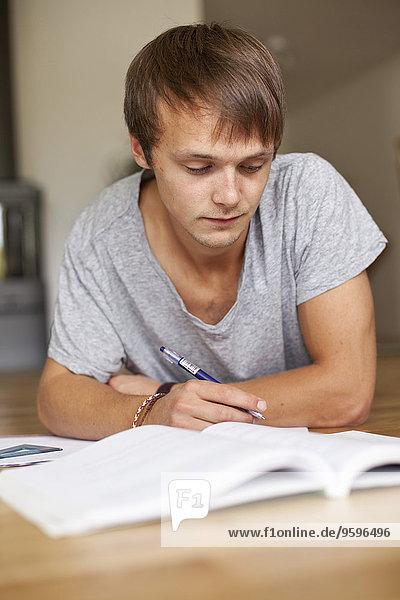 Junger Mann studiert  während er zu Hause auf dem Boden liegt.