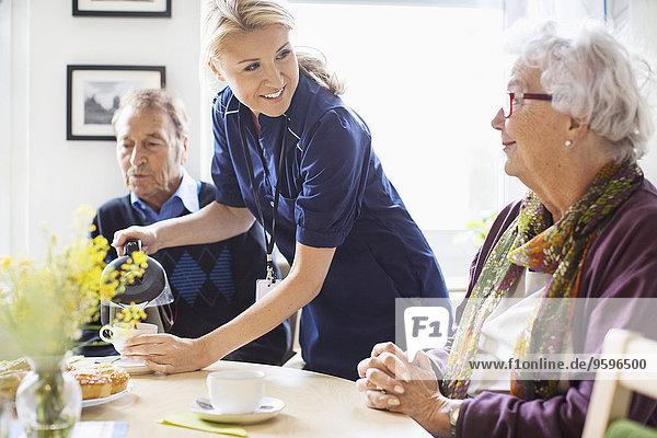 Fröhliche Frau serviert Kaffee für Senioren im Pflegeheim