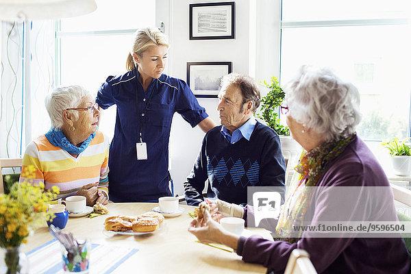 Frau mit Senioren diskutiert am Frühstückstisch im Pflegeheim