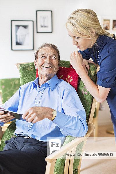 Glücklicher älterer Mann  der weiblich aussieht  während er digitale Tabletten im Pflegeheim benutzt.