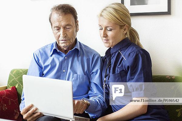 Weiblicher und älterer Mann mit Laptop im Pflegeheim