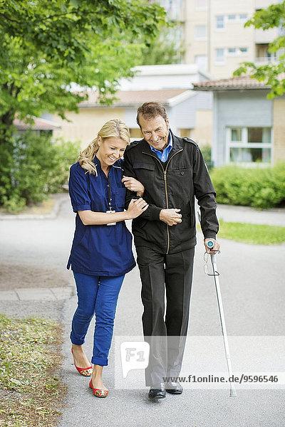 Volle Länge des glücklichen weiblichen Gehens mit behindertem älteren Mann auf der Straße