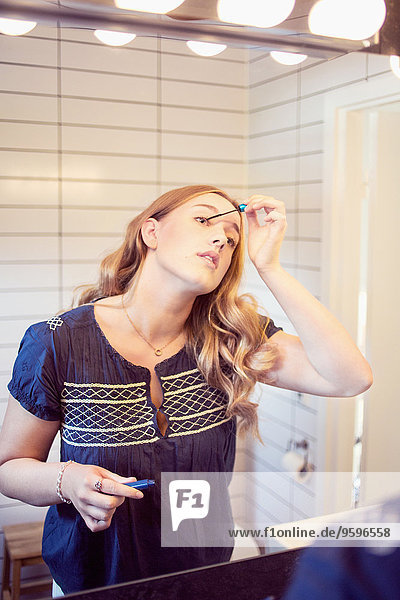 Junge Frau mit Mascara im Bad