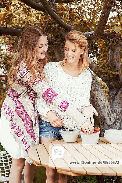 Glückliche Schwestern bereiten Smoothie am Tisch im Freien vor
