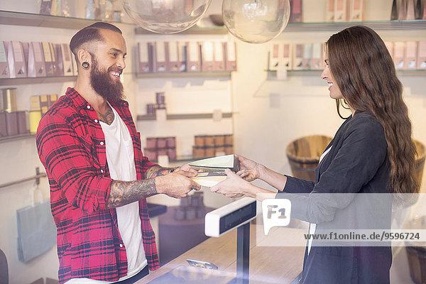 Glücklicher Besitzer schenkt dem Kunden im Geschäft Süßigkeiten