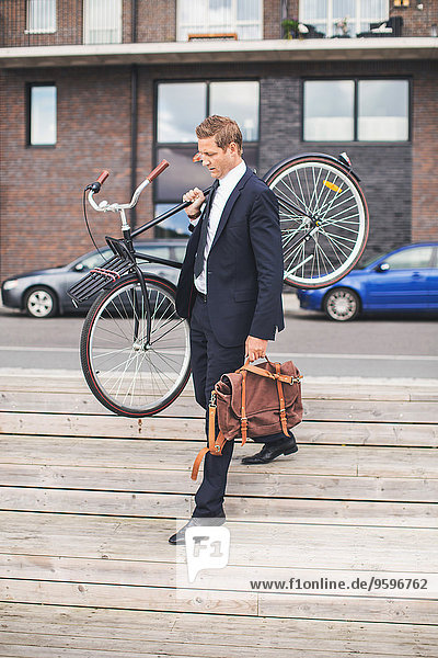 Full length of businessman carrying bicycle while walking on steps