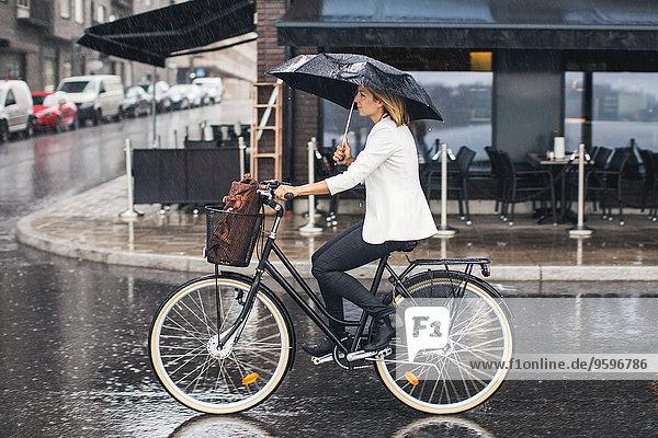 Geschäftsfrau fährt in der Regenzeit mit dem Fahrrad auf der nassen Stadtstraße.