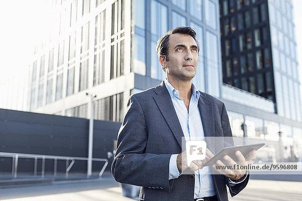 Zuversichtlicher Geschäftsmann schaut weg  während er ein digitales Tablett außerhalb des Bürogebäudes benutzt.
