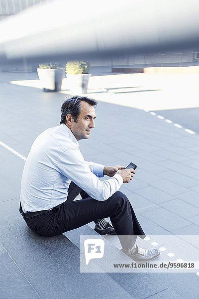 Seitenansicht des Geschäftsmannes bei der Benutzung des Mobiltelefons auf der Treppe