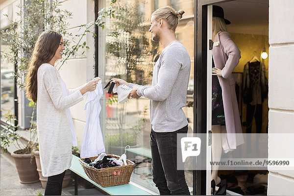 Happy Male Besitzer zeigt dem Kunden den Preis des Schuhs außerhalb der Boutique.