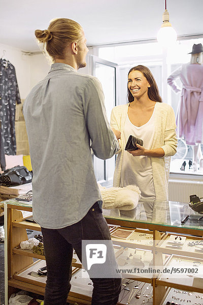 Happy female customer standing with male owner at checkout counter in boutique