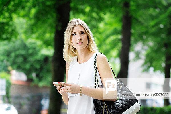 Junge Frau hält Handy in der Hand  während sie nach draußen schaut.