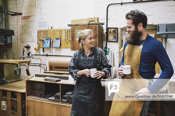 Handwerker und Frau beim Plaudern in der Pfeifenorgel-Werkstatt