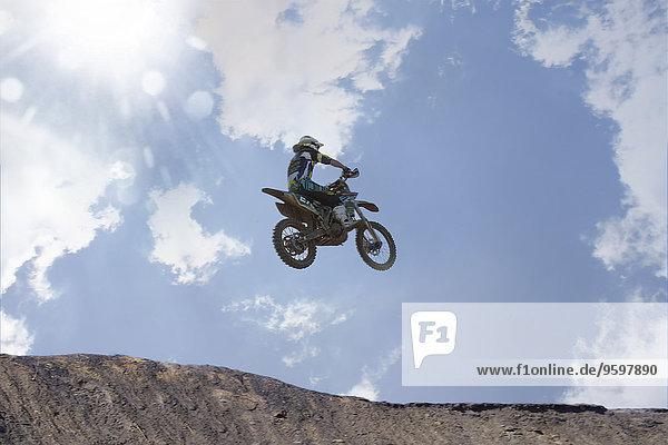 Silhouettierter junger  männlicher Motocross-Rennfahrer  der über den Schlammberg springt.