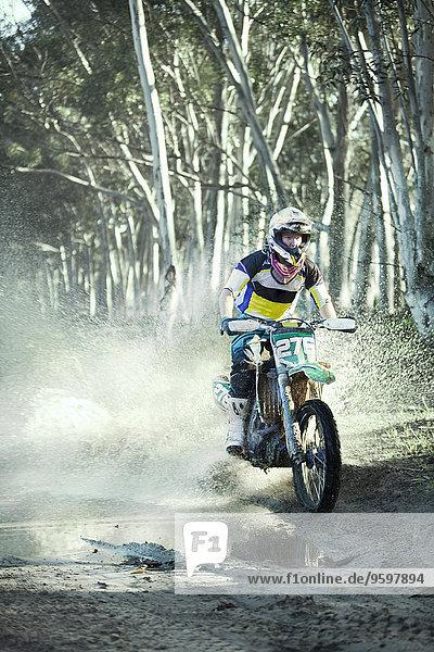 Junger männlicher Motocrosser fährt durch die Pfütze im Wald