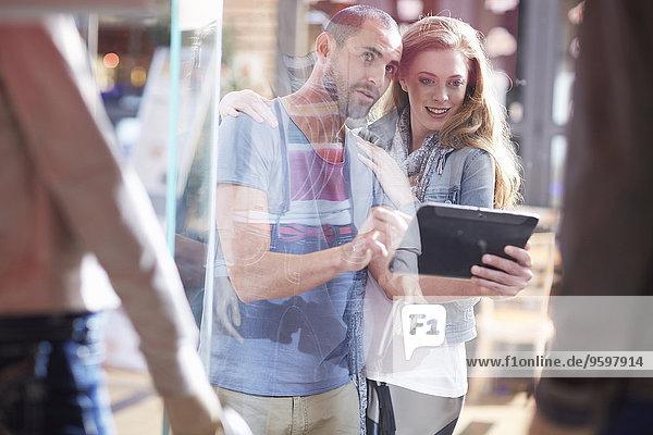 Paar beim Schaufensterbummel  mit digitalem Tablet
