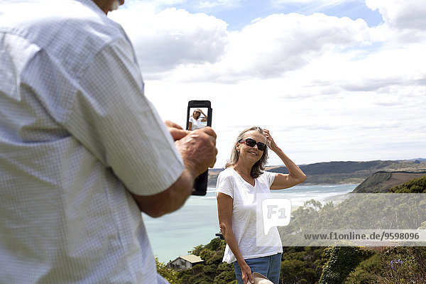 Ehemann fotografiert Frau  Ozean im Hintergrund  Raglan  Neuseeland