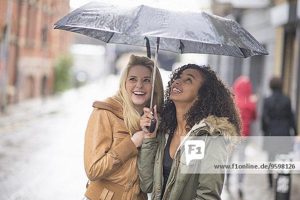 Junge Frauen  die sich unter dem Regenschirm verstecken