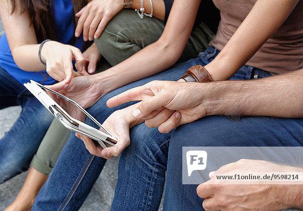 Gruppe von Freunden  die sich das digitale Tablett anschauen  konzentrieren sich auf Tablett und Hände