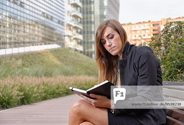 Junge berufstätige Frau auf der Bank sitzend  im Notizbuch schauend