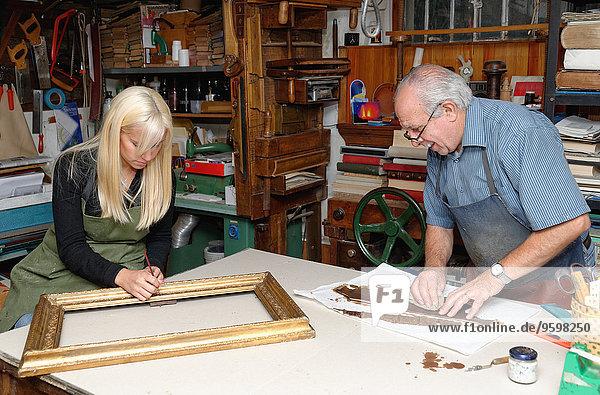 Senior Mann und junge Frau beim Restaurieren von Bilderrahmen und Buchrücken in der traditionellen Buchbinderei