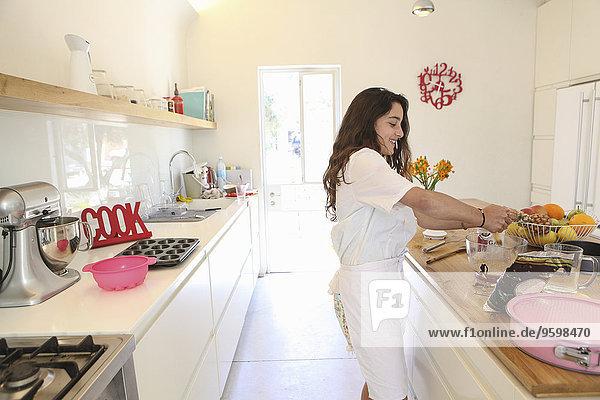 Teenager Mädchen in weißer Schürze Backen Kuchen in der Küche
