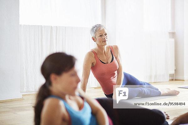 Zwei Frauen  die in der Pilates-Klasse auf der Seite liegen.
