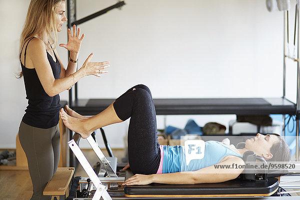 Tutorin  die eine Studentin unterrichtet  die auf einem Reformer in einem Pilates-Studio liegt.