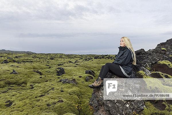 Mittlere erwachsene Frau auf Felsen sitzend  Blick auf das Blafjoll  Island