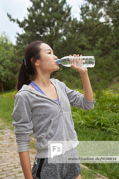 Junge Läuferin trinkt Flaschenwasser im Park