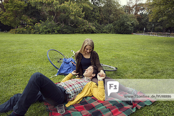 Young couple holding hands on picnic blanket in park