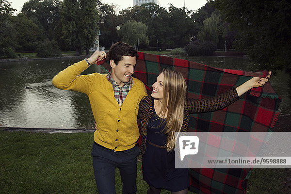 Young couple holding up blanket in park